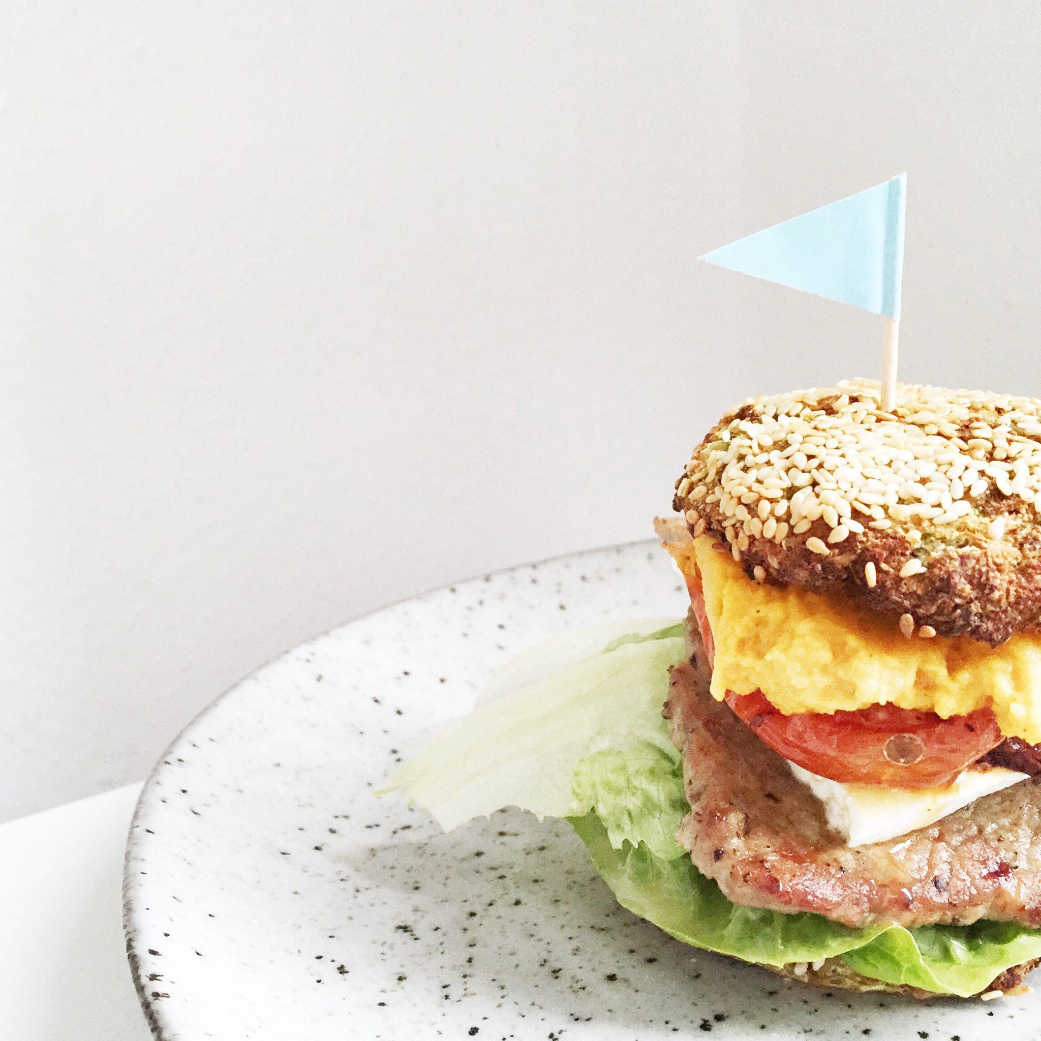 Burger set fra siden med flag i toppen. Serveret på tallerken fra House Doctor.