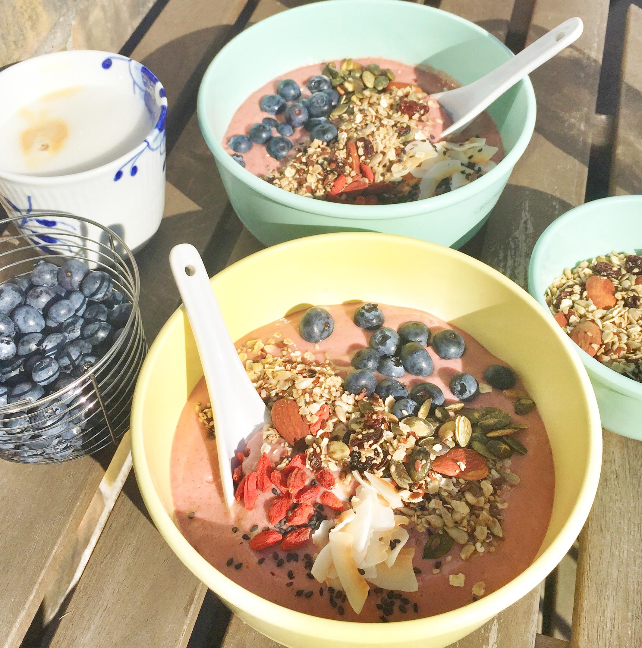 Jordbær smoothie bowl på altanen i solen med kaffe og blåbær