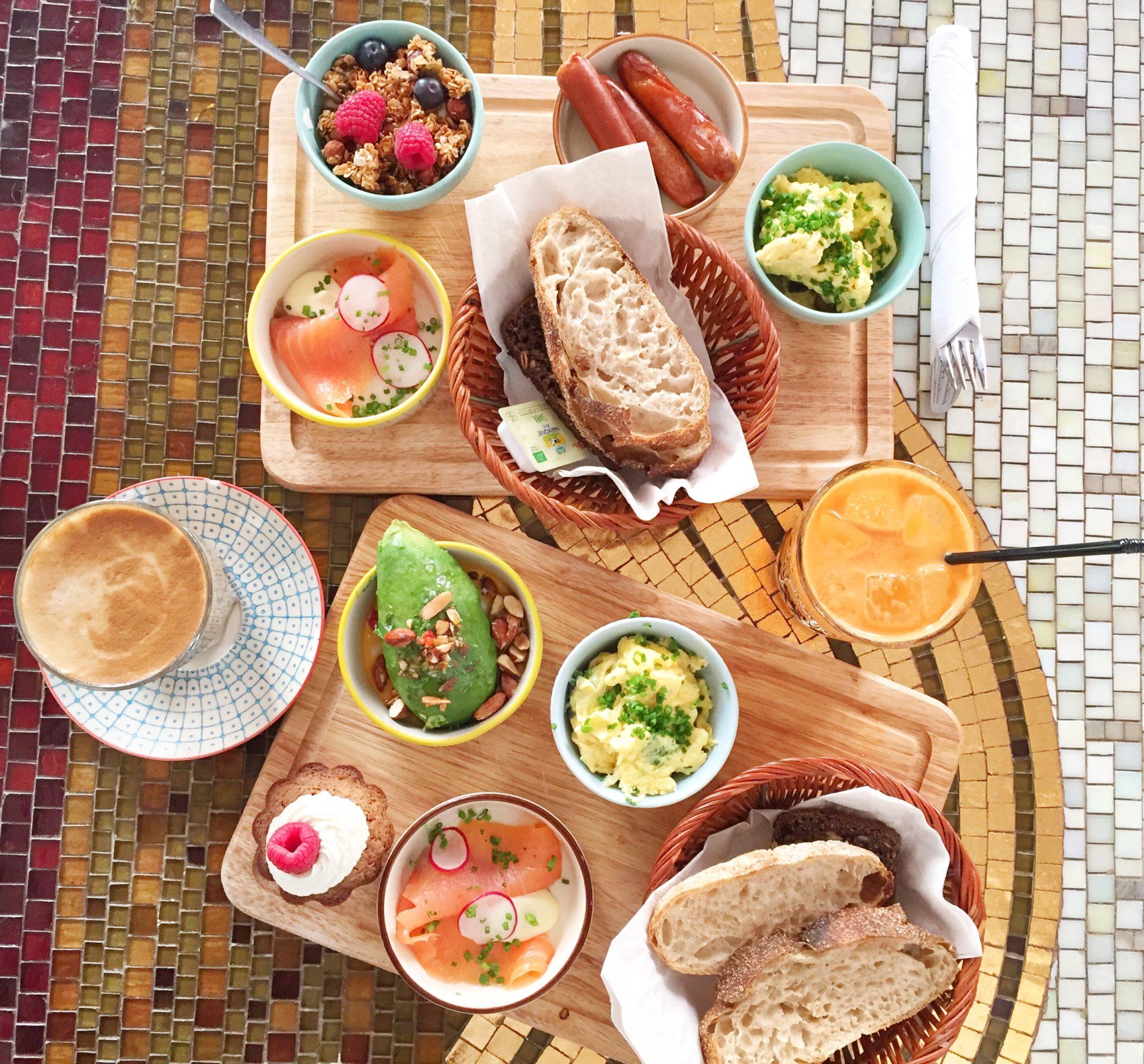 Bland selv brunch. Juice, æg, avokado, kage, laks, brød. Mad Og Kaffe i København