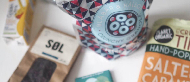 Produkter fra online webshop Greenos; Chokolade, tang, popcorn på et hvidt bord bestilt over nettet