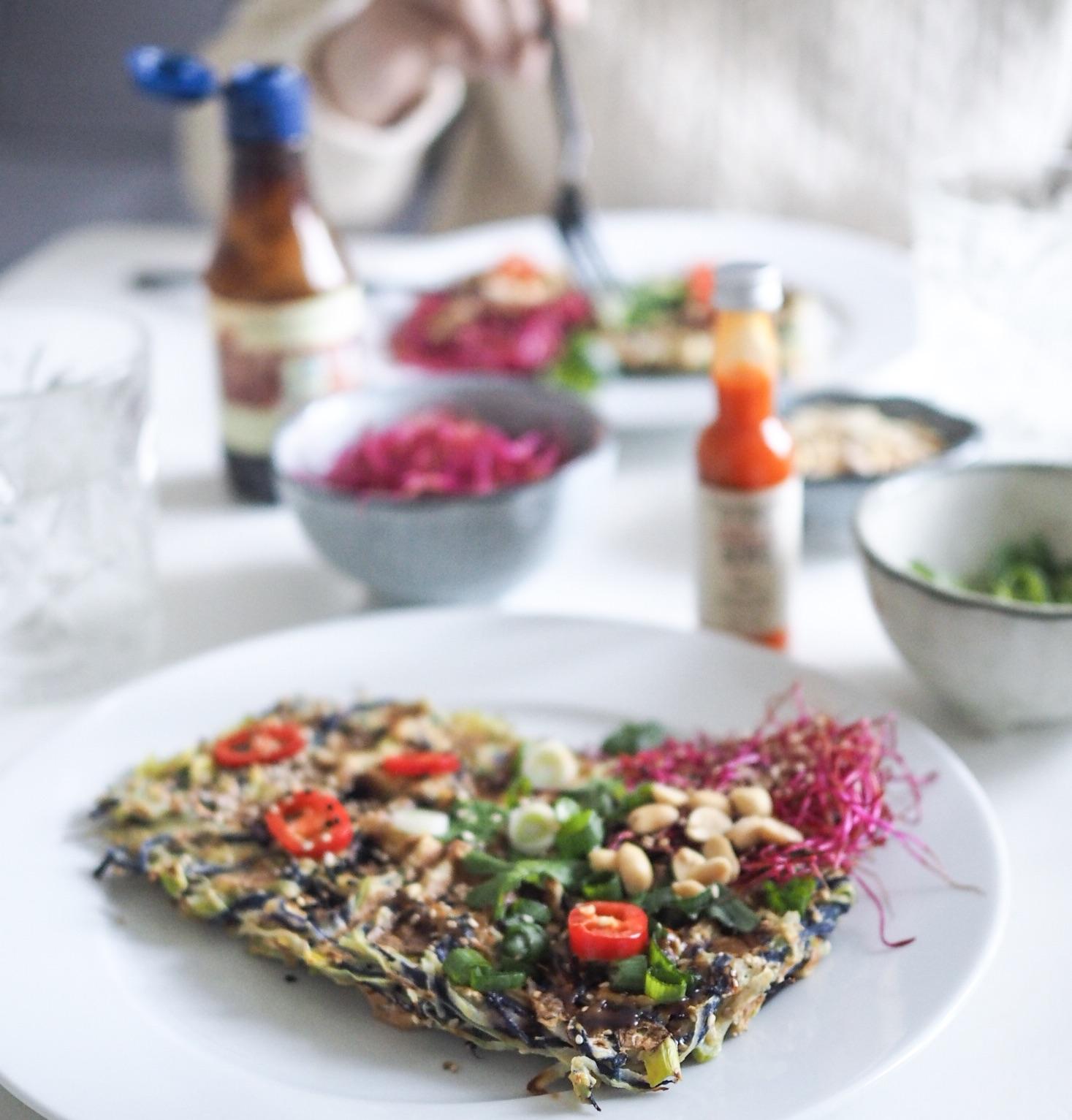Okonomiyaki vafler med hoisinsauce og koriander. Billede hvor der er en der spiser. Hoisinsauce i baggrunden og middag for to