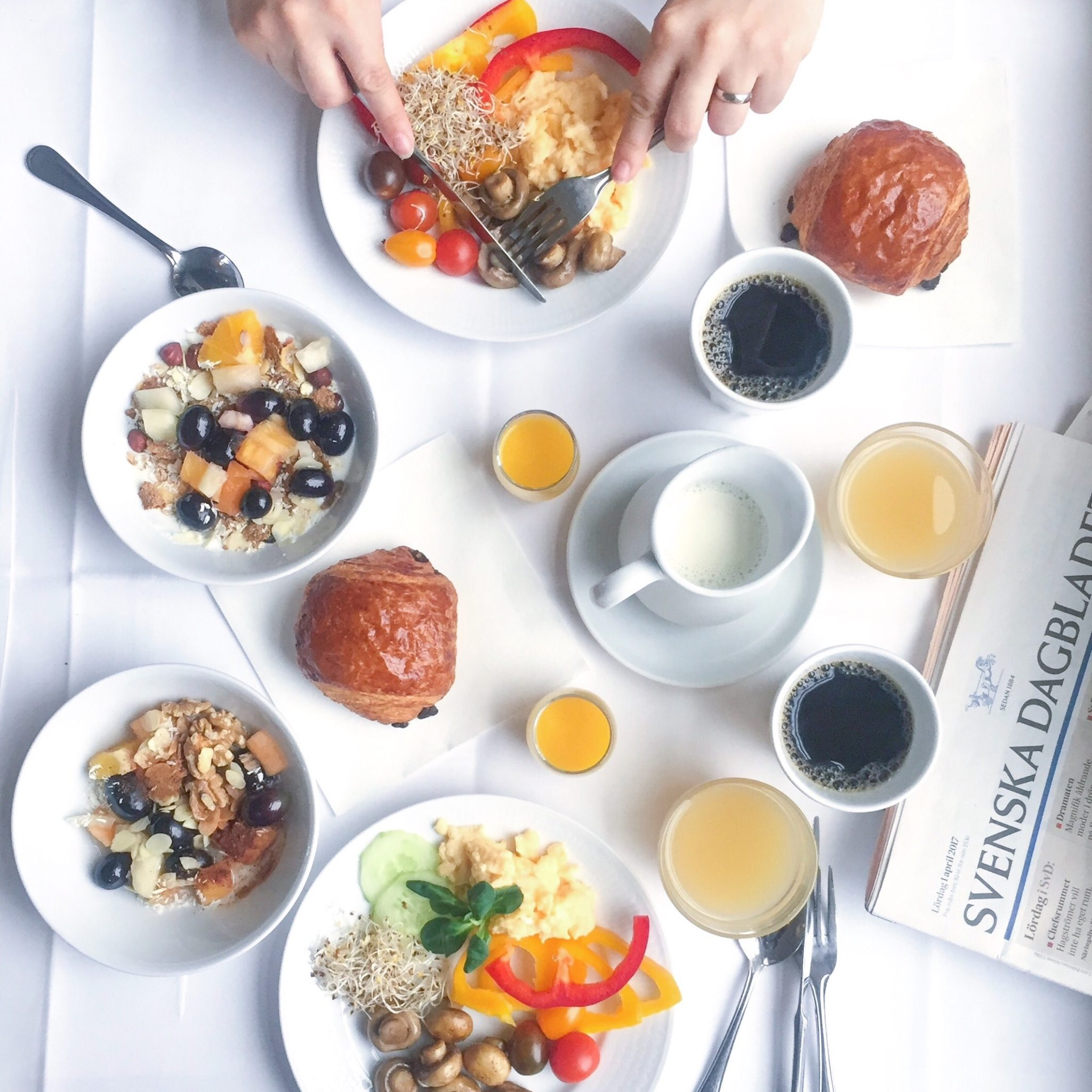 Hotelmorgenmad med æg, frugt, nødder, pain au chocolat, kaffe, juice, svensk avis. Med hvid baggrund