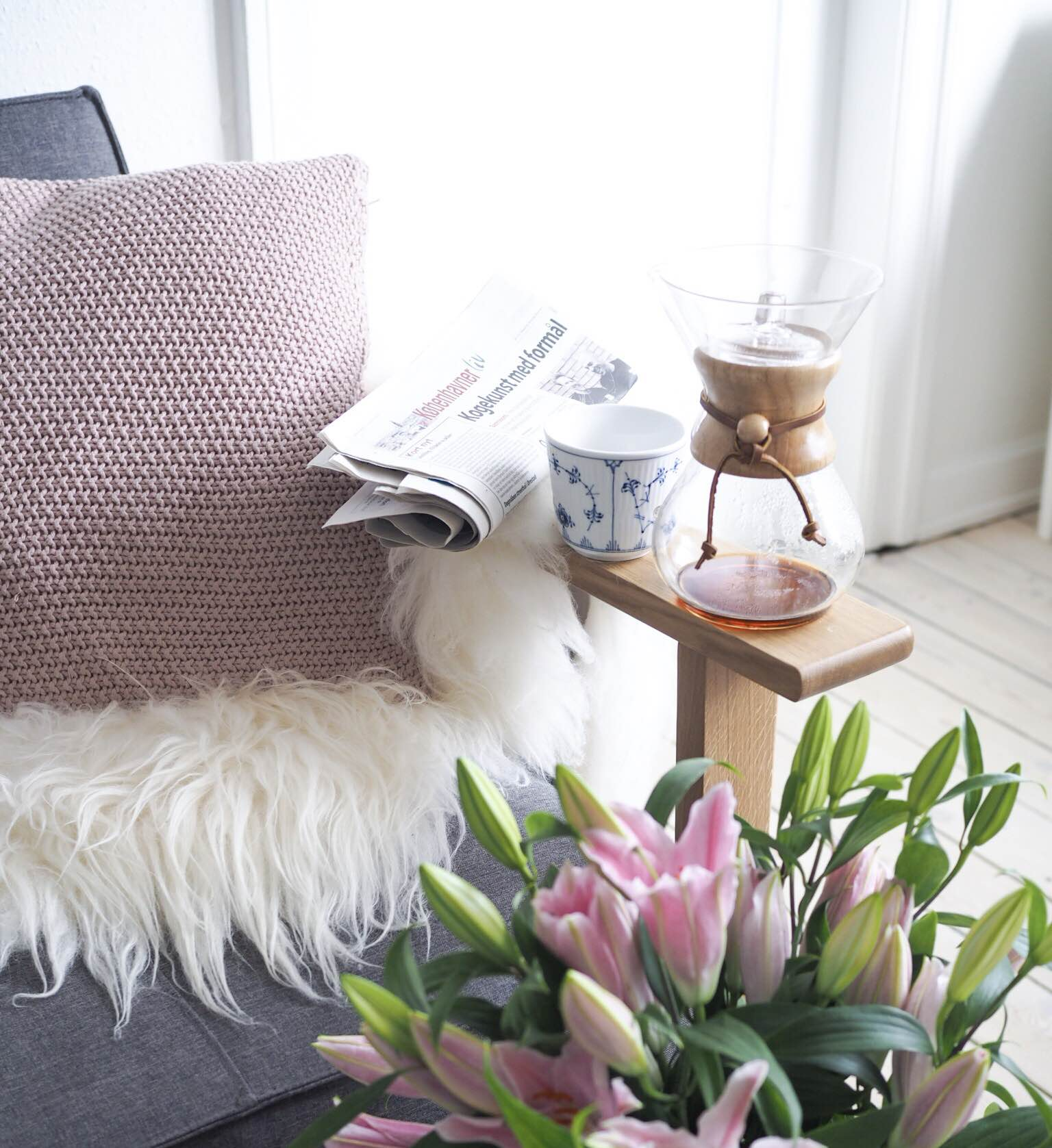 Dansk hygge, danish hygge med kaffekande fra Chemex, en stor buket lyserøde liljer, grå sofa, islands skind og puder fra Magasin.