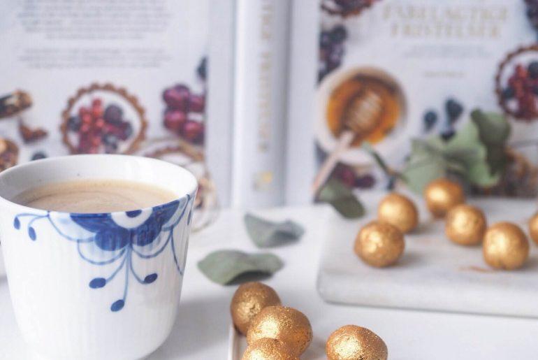 sunde romkugler med dadler, bønner og guld. Kop fra Royal Copenhagen med kaffe og havremælk. Bog fra Emma Martiny; Fabelagtige fristelser
