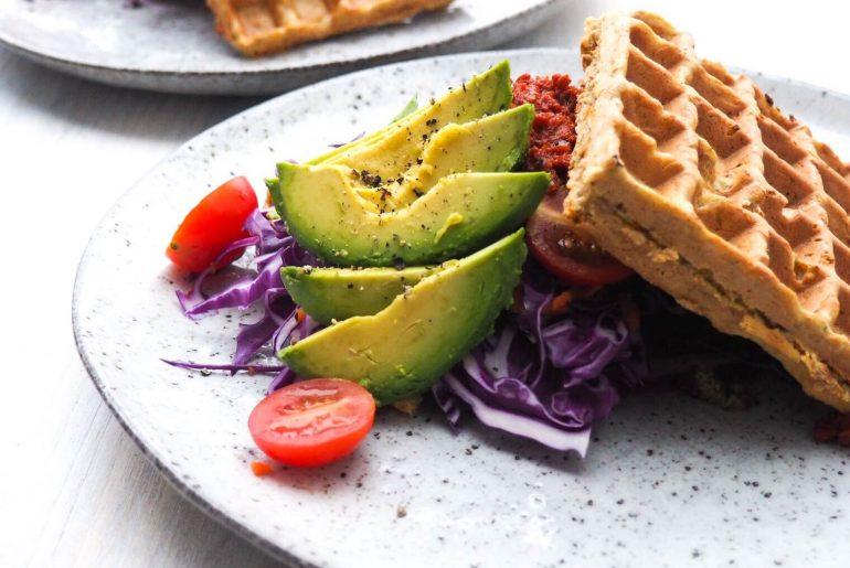 Sunde sandwichvafler med avokado, hummus, rødkål, soltørrede tomater, tomater