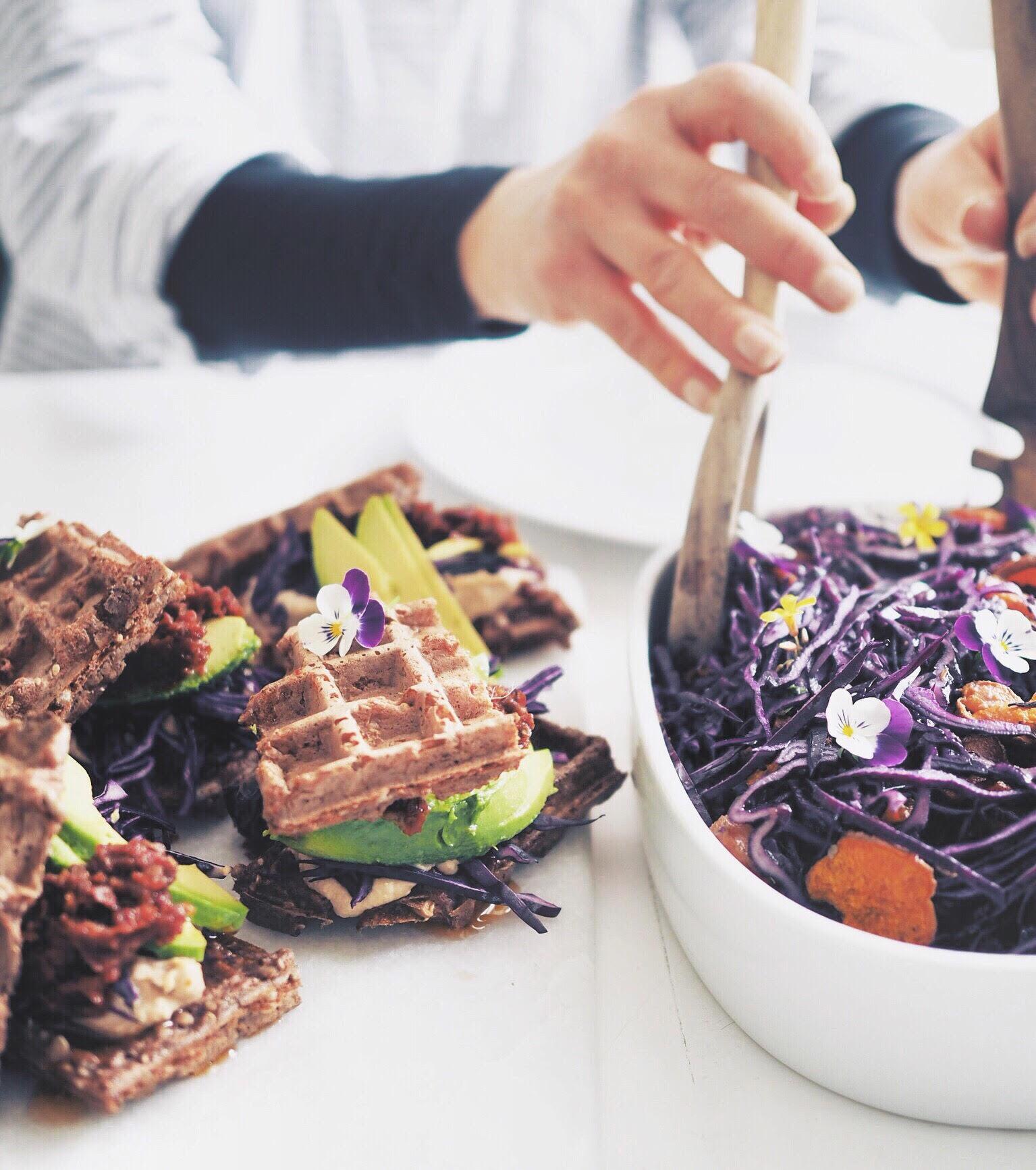 Opskrift på rødkålssalat med gulerødder, sød kartoffel og tahindressing. Toppet med spiselige blomster og serveret med en vaffel sandwich med hummus, avokado og soltørrede tomater. Alt sammen vegansk frokost