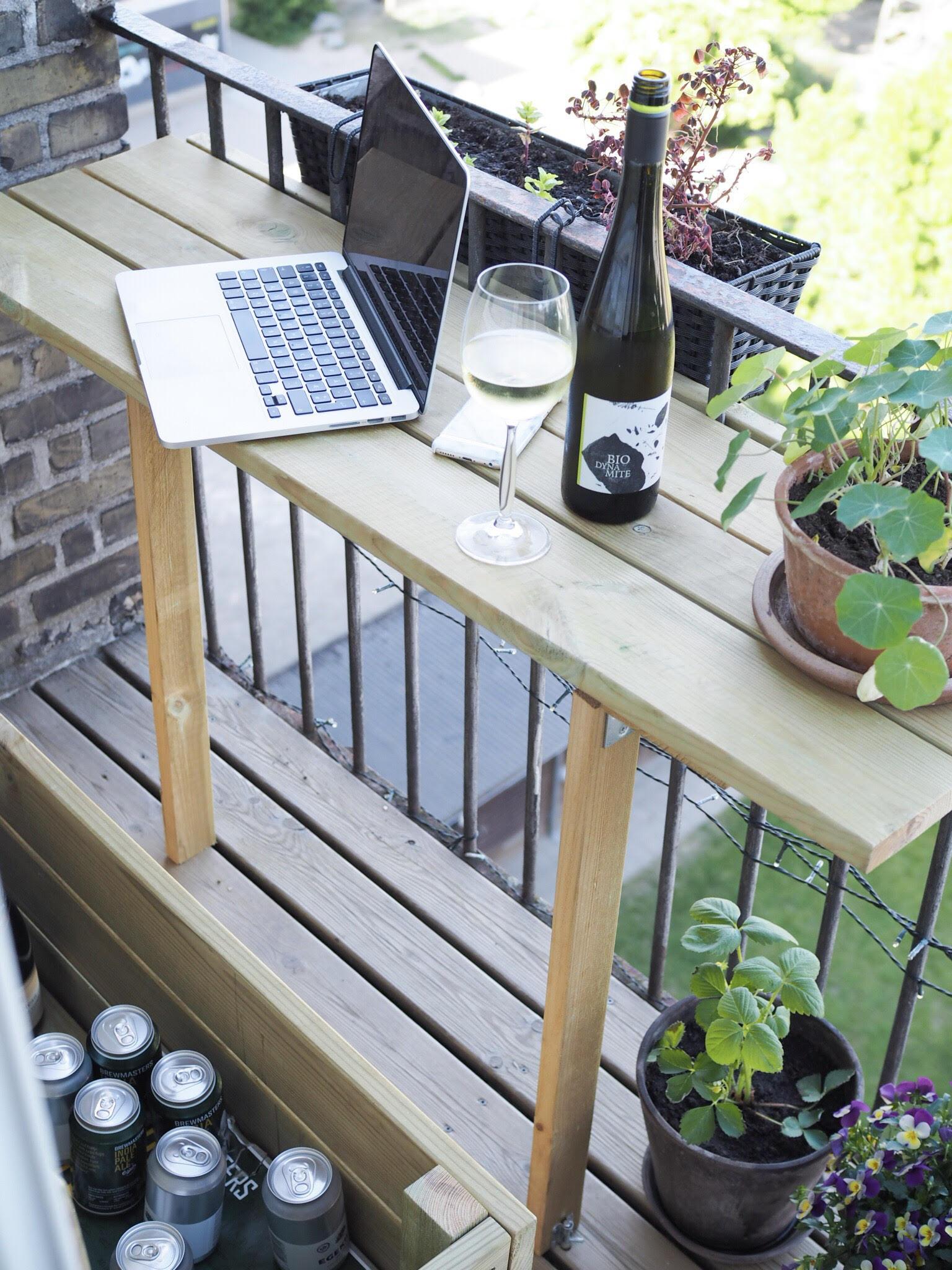 Altanliv og kold hvidvin på Østerbro. Computer på altanen og et klap op-altanbord med grønne planter på en sommerdag i maj
