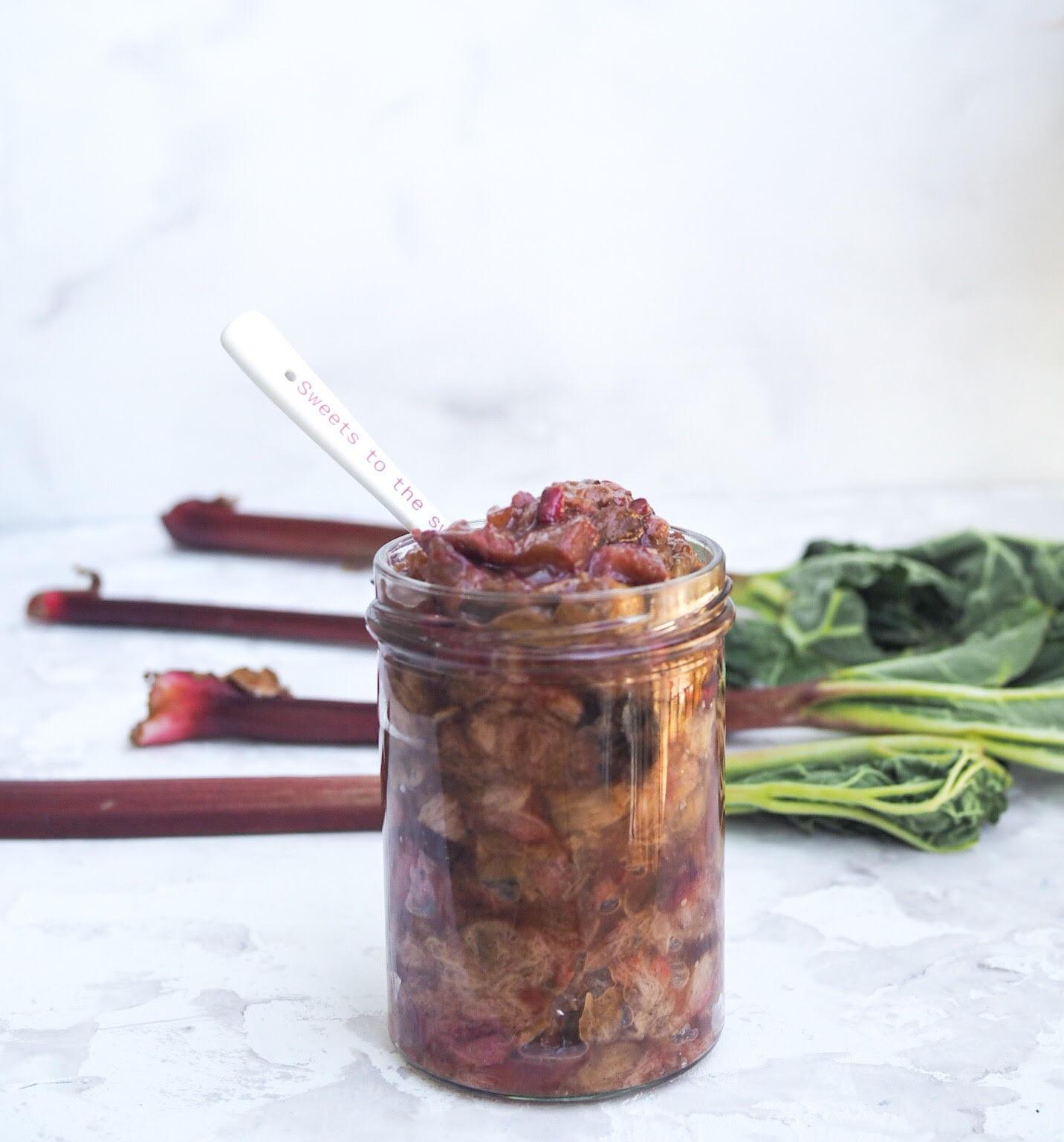 Opskrift på rabarberkompot med ingefær i ovn. Syltetøjsglas med kompot og rabarber i baggrunden. Hvid baggrund