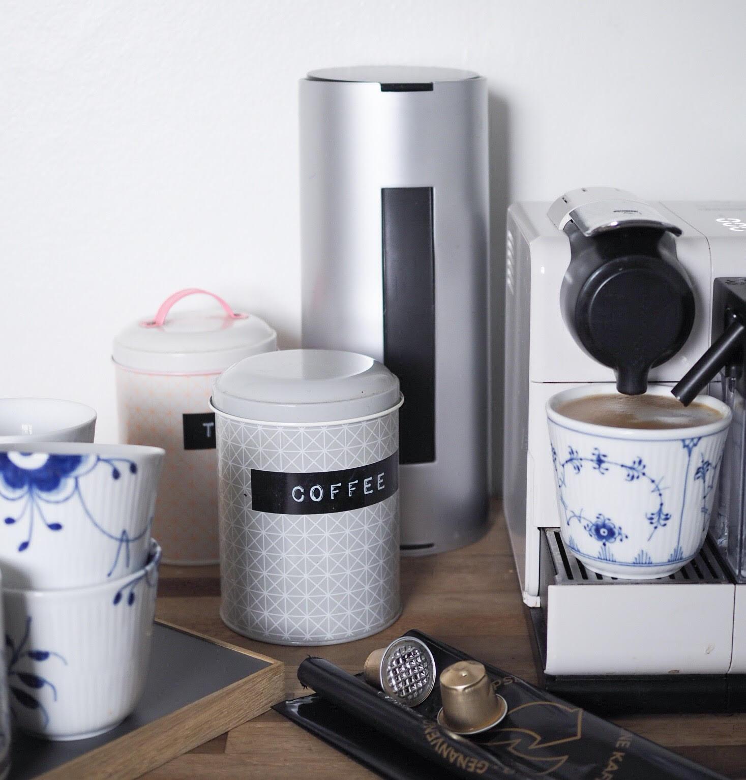 Nespresso kaffemaskine med mælkeskummer - model Lattissima. Bøtter fra Bloomingville og kaffekopper fra Royal Copenhagen. Holder til brugte kapsler og pose til genanvendelse